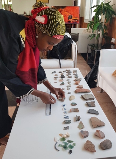 Dr Sada Mire analysing surface collection from Berbera archaeological site with Medieval Chinese ceramics and Venetian perfume bottles, 2018